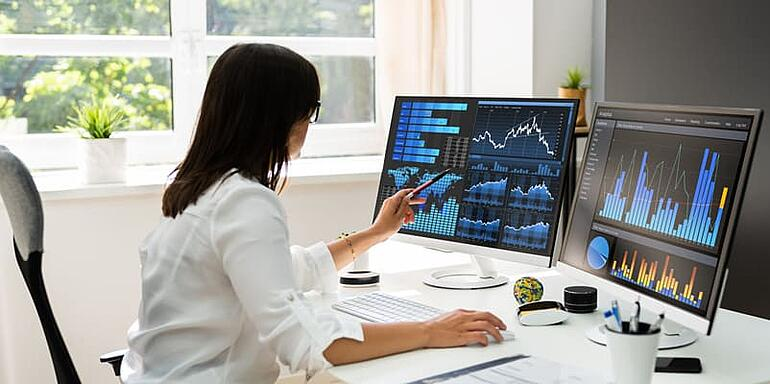 An IT manager (woman) analyzing Help Desk Metrics & KPIs dashboards and analytics to improve performance and drive innovation to the business