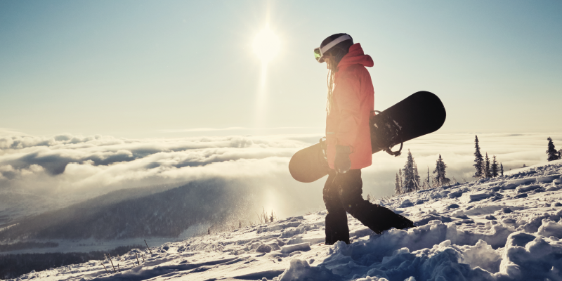 Accounts Payable Outsourcing Case Study: A person walking in the snow with a ski board and the sun in the background.